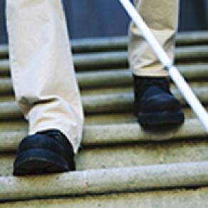 En man med vit käpp går ner för en trappa, man ser endast fötterna. Fotografi